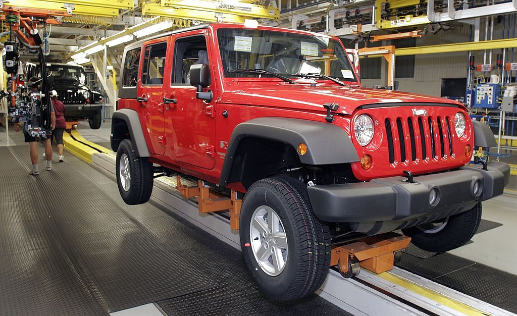 A Jeep Wrangler with a hard top on the assembly line