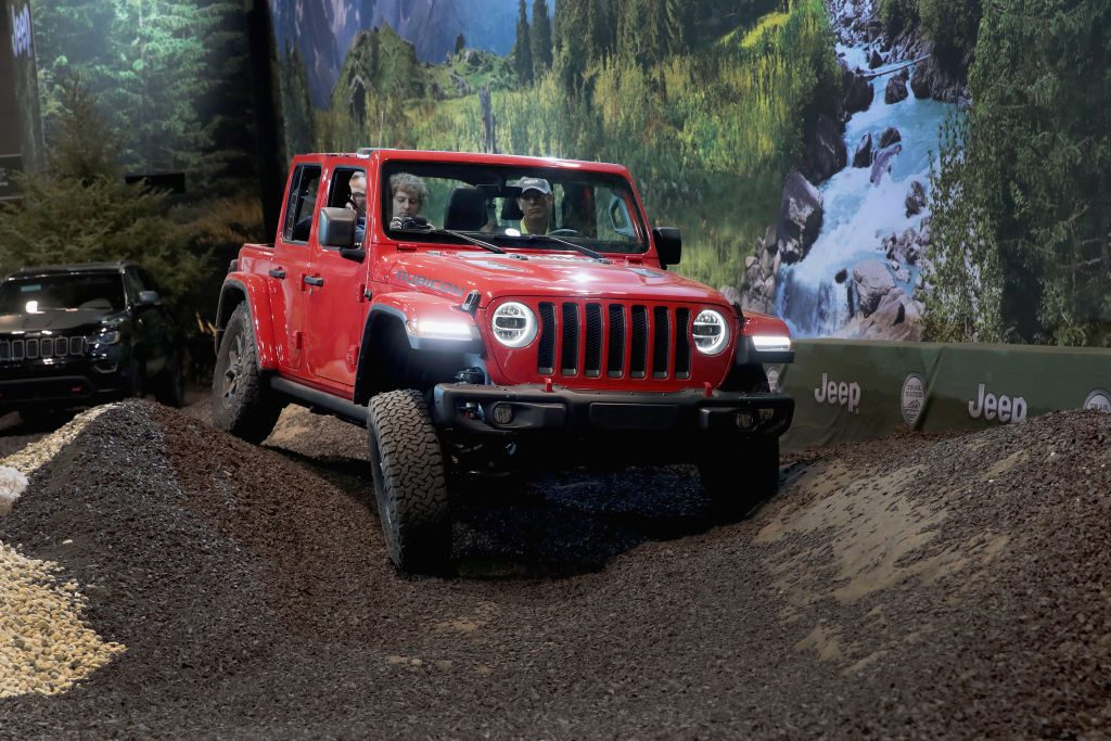 A person testing driving a Jeep Wrangler Rubicon at an auto show