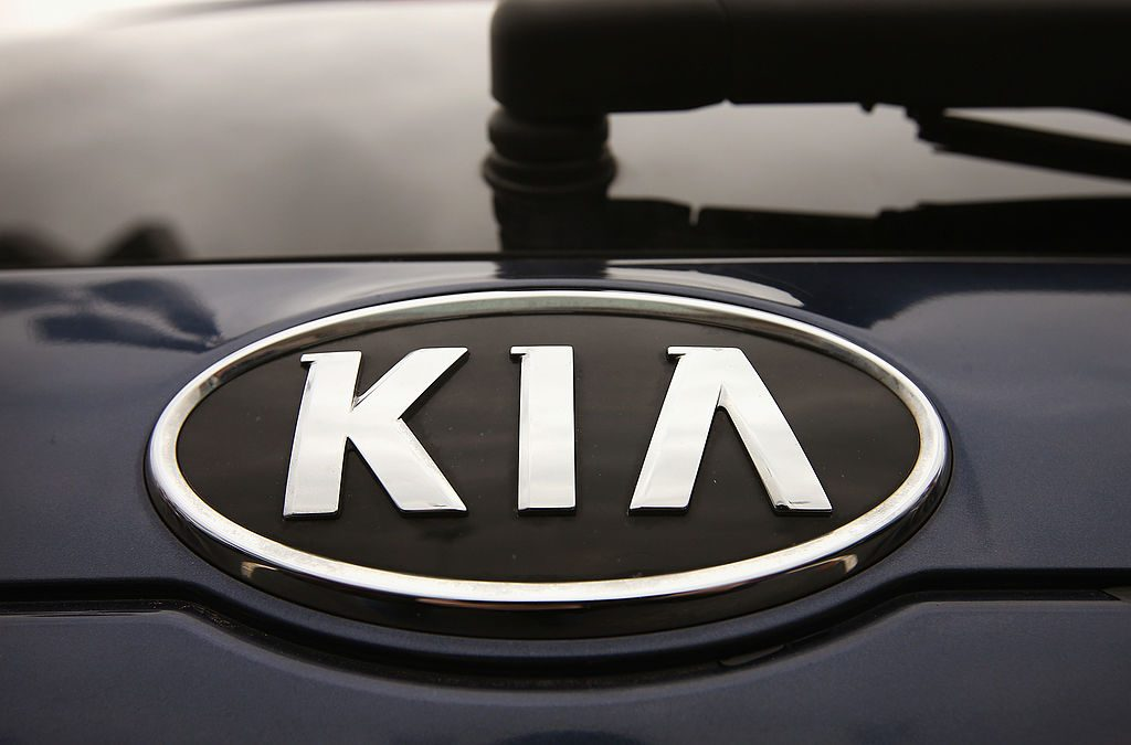 The logo on a Kia Sedona for sale at a Kia dealership.