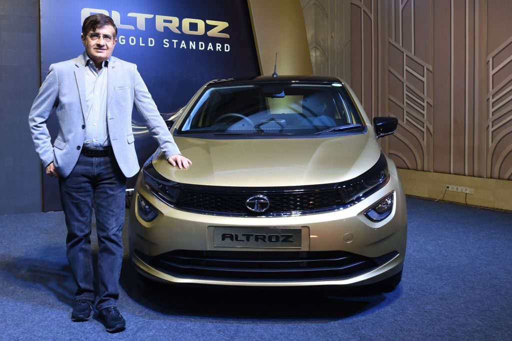 The President of Tata Motors stands next to one of the company's cars