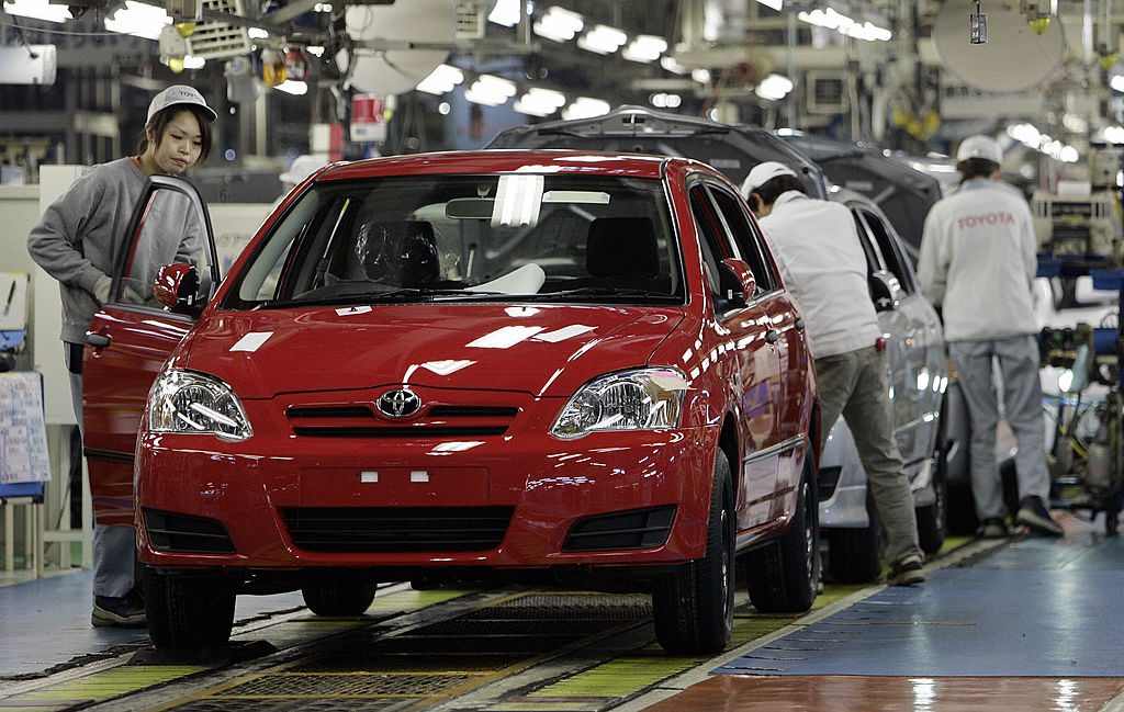 Workers inspect Toyota Corollas at a factory