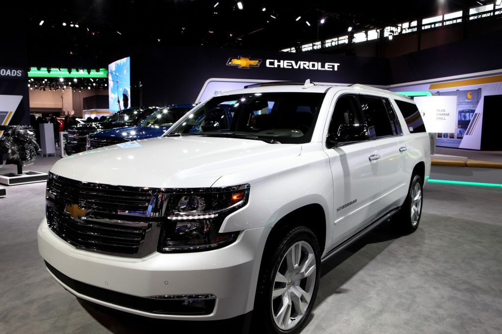 A white Chevy Suburban on display at an auto show