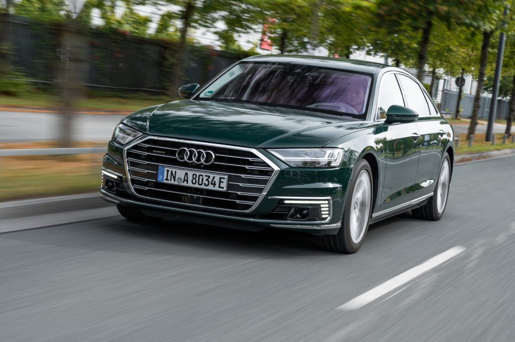 a green Audi A8 hybrid driving at speed on the road