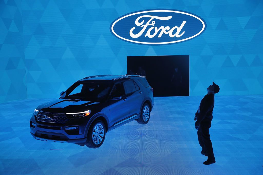 Workers prepare for a demonstration featuring the new 2020 Ford Explorer at the North American International Auto Show