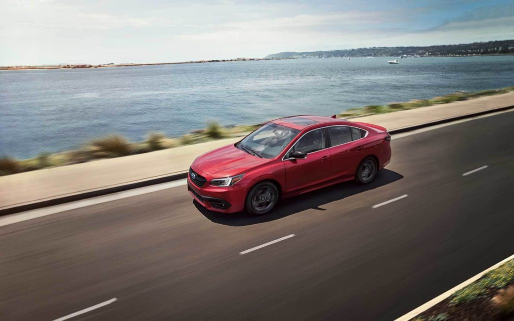A red 2020 Subaru Legacy Sport cruising down the highway.