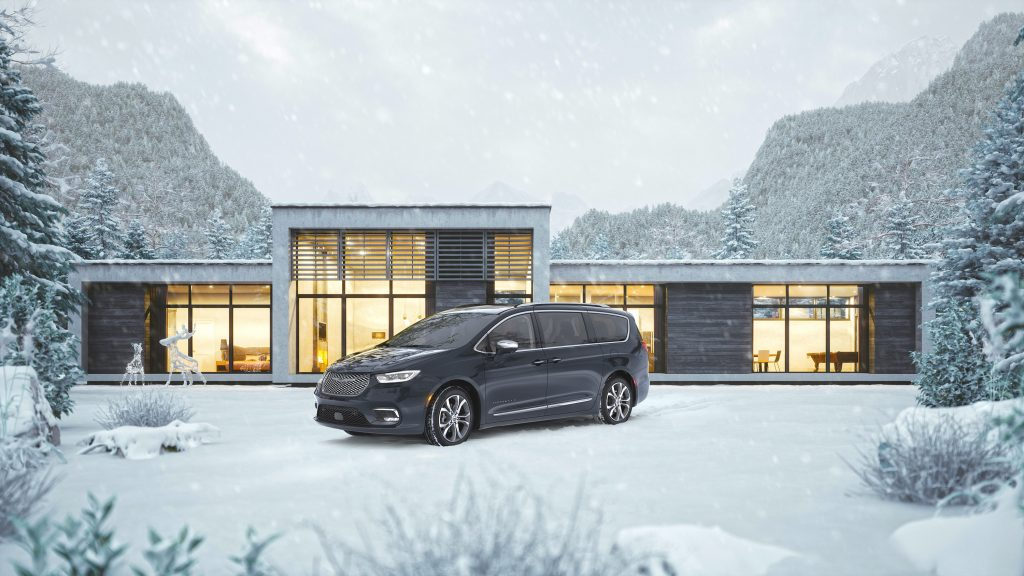 a refined looking black Pacifica in front of a modern home in the snow