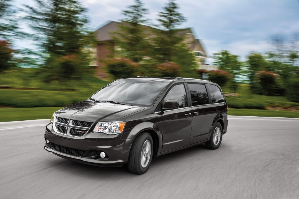 a black Dodge Caravan by FCA in motion
