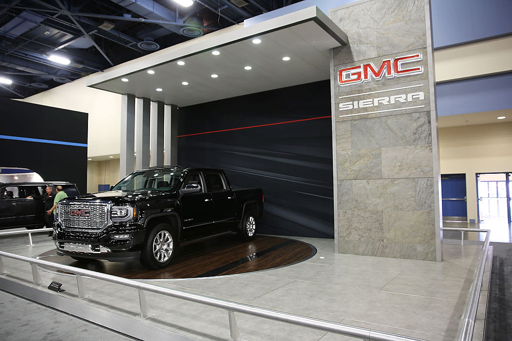 a black GMC Sierra truck on display at an auto show