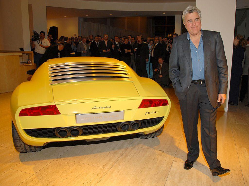 Jay Leno posing next to a Lamborghini Miura concept car