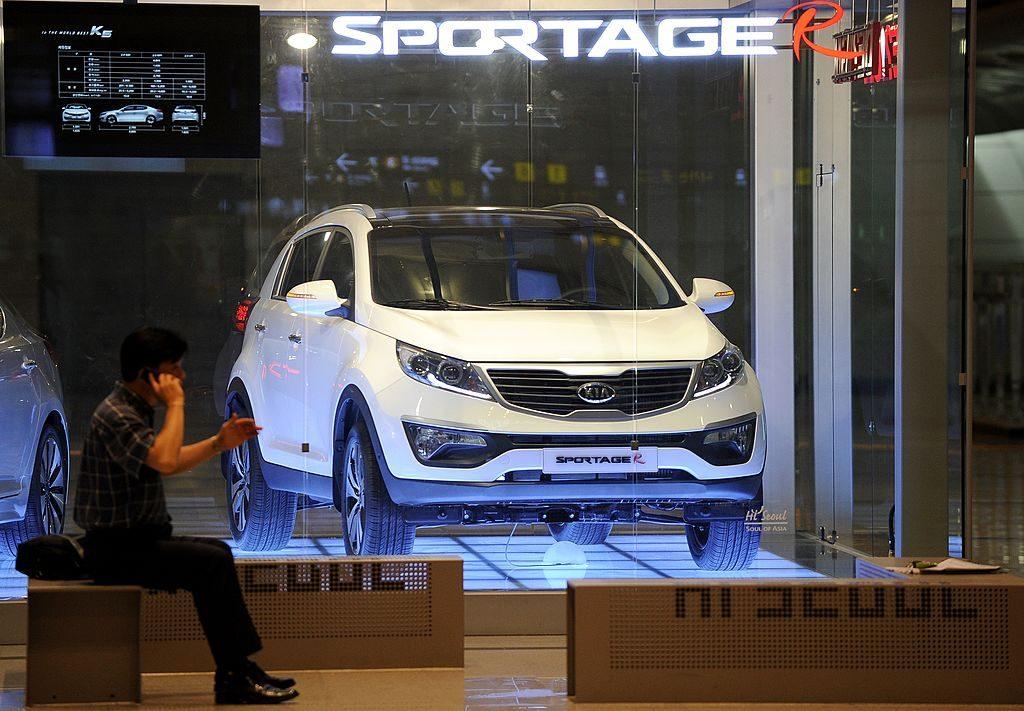 A man sitting next to a Kia Sportage