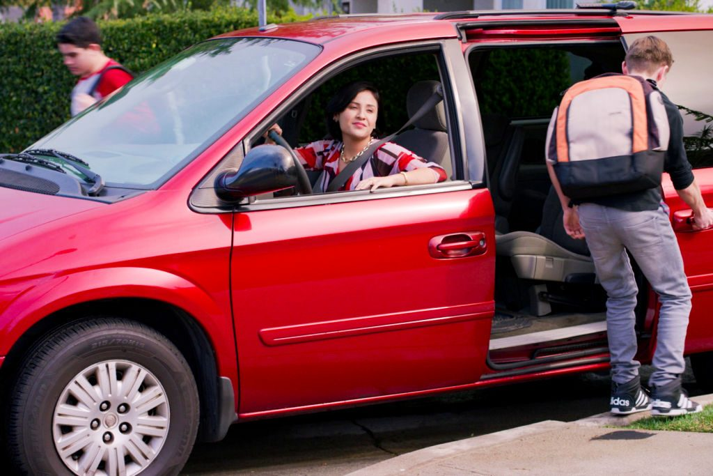 A mom picking up her kids in a minivan