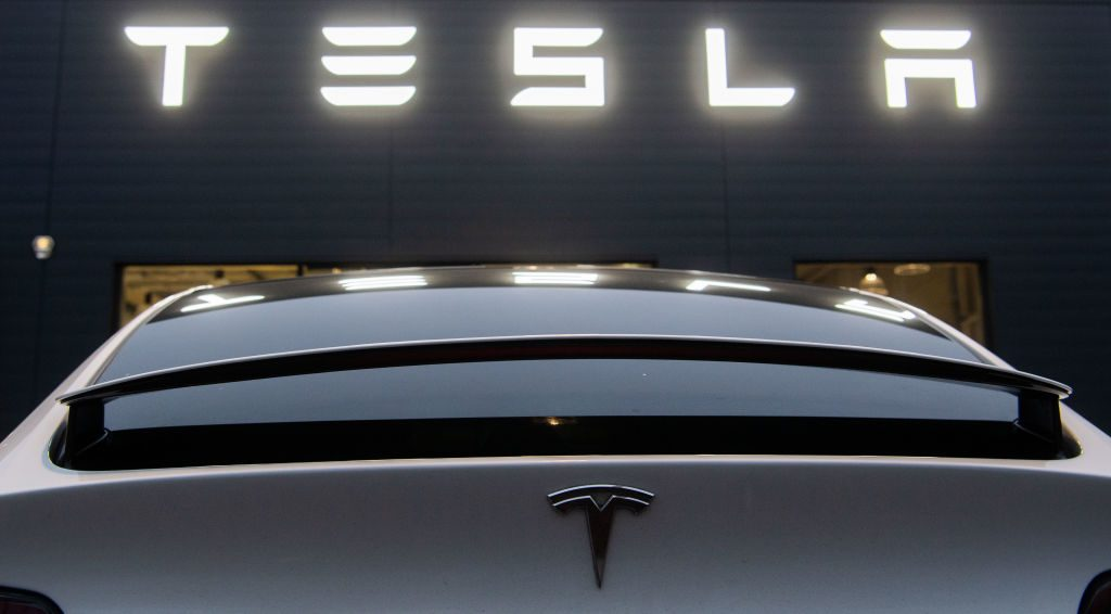 A Tesla Model X stands in front of a sales shop and service center of the manufacturer of electric vehicles, Tesla