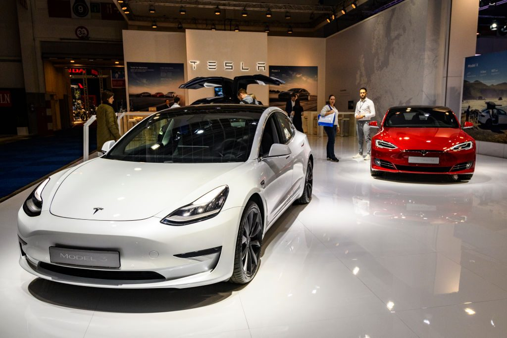 Tesla Model 3 compact sedan car in white with a Tesla Model S dual motor all electric sedan on display at Brussels Expo