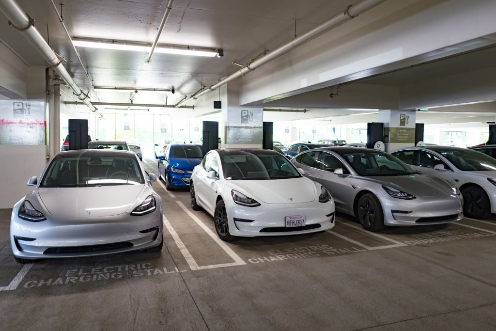 Tesla model 3 cars charging in a parking garage