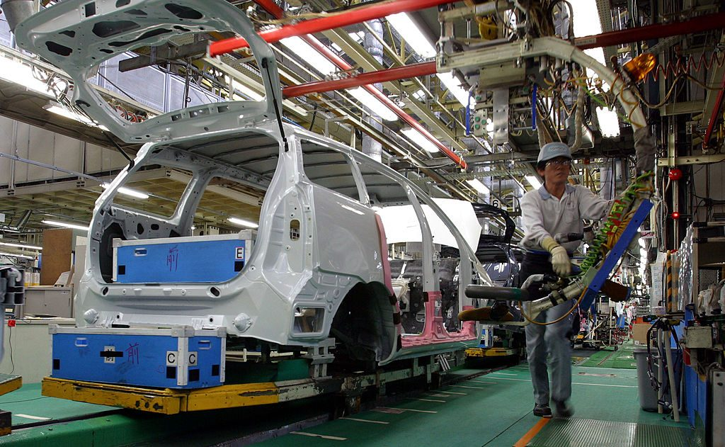 Toyota Motor Corporation employees assemble a car at the Tsutsumi Plant February 20, 2003 in Tokyo