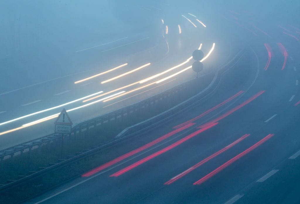 Vehicles are driving in the morning in fog