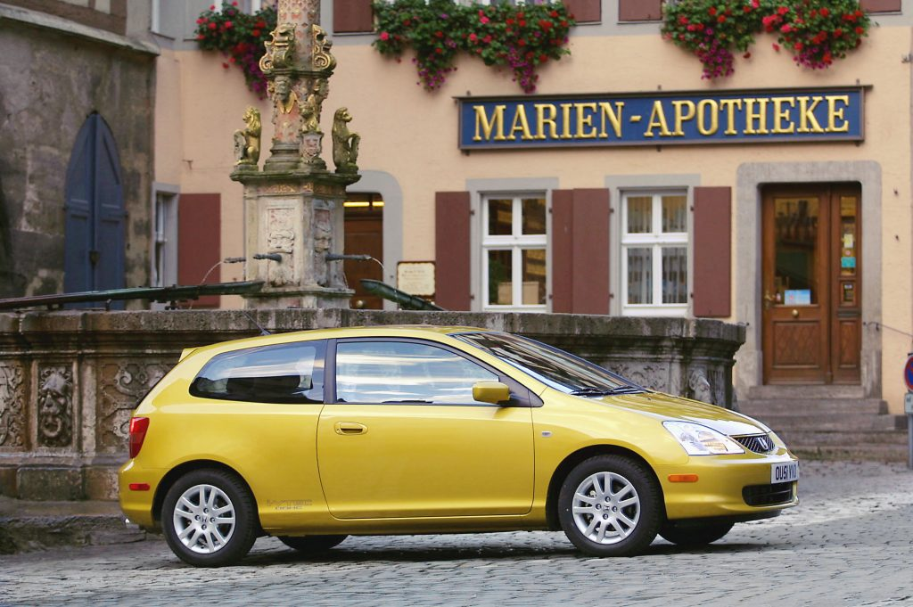 A golden yellow Honda Civic Si hatchback parked in a quaint European village.