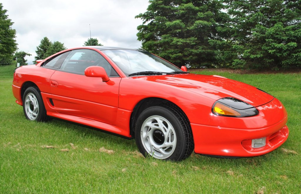 A red 1991 Dodge Stealth R/T parked in a pretty grassy lawn.