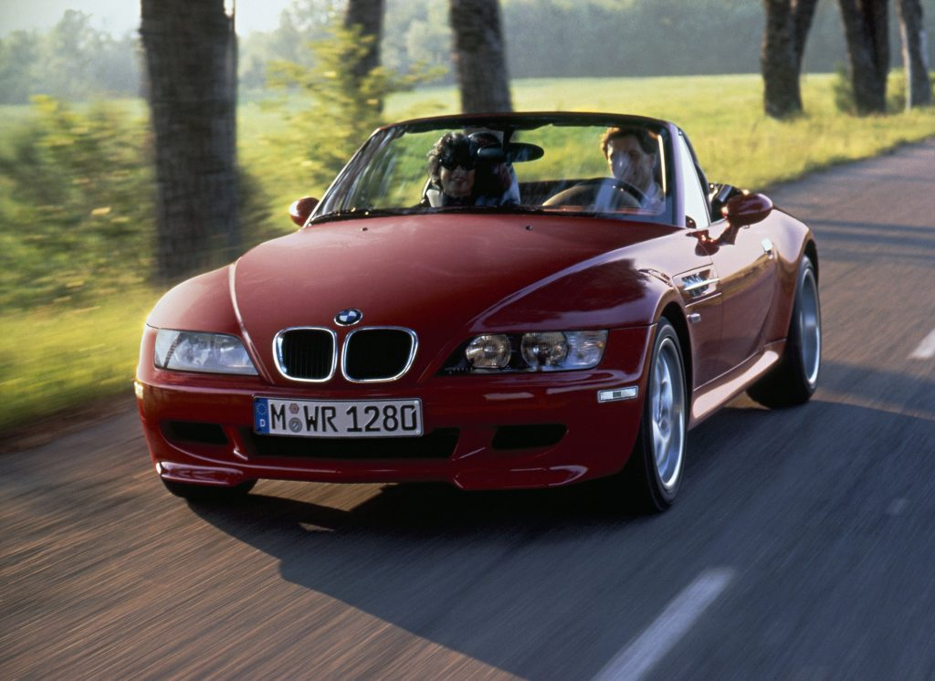 A red 1998 BMW Z3 M Roadster driving down a scenic country road.