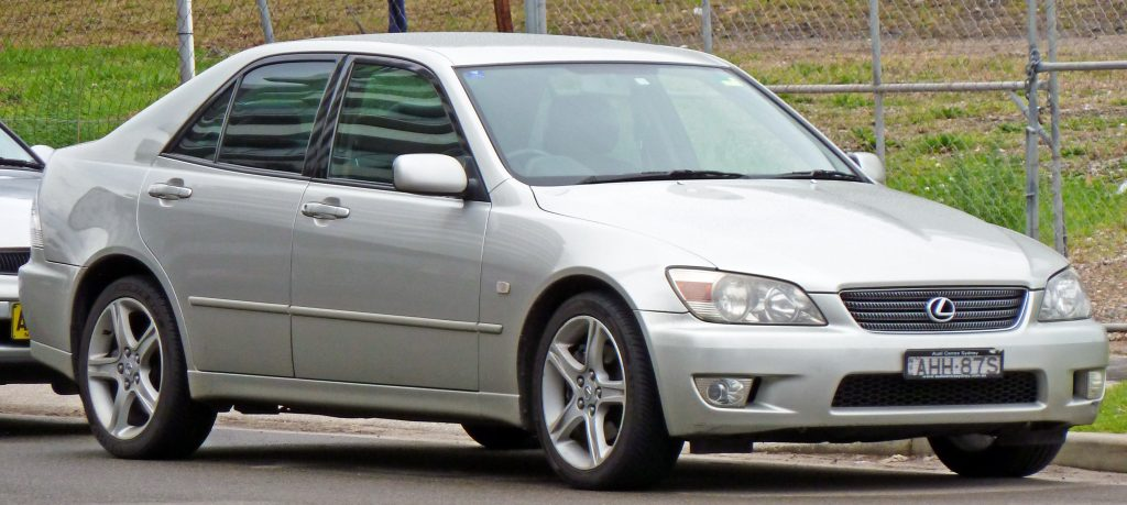 A silver 2001 Lexus IS 300 parked by the side of a country road.