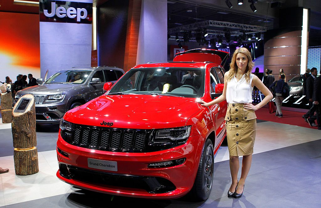 A model poses next to a Jeep Grand Cherokee during the second press day of the Paris Motor Show