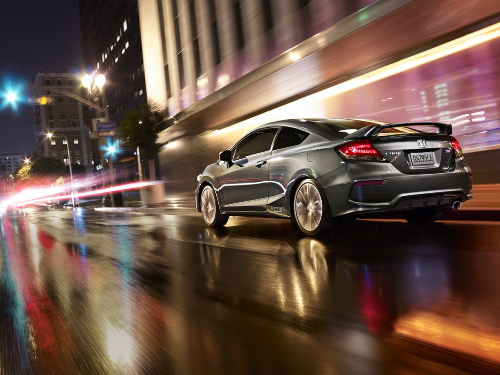 A silver 2015 Honda Civic Si Coupe driving down a wet urban highway.