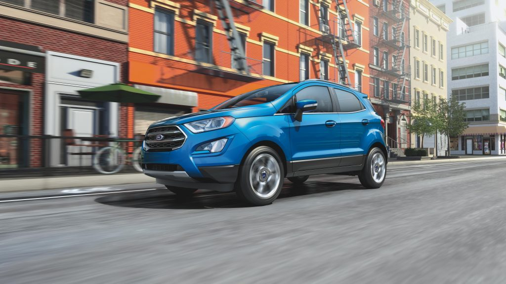 A blue 2020 Ford EcoSport crossover driving down an urban street.