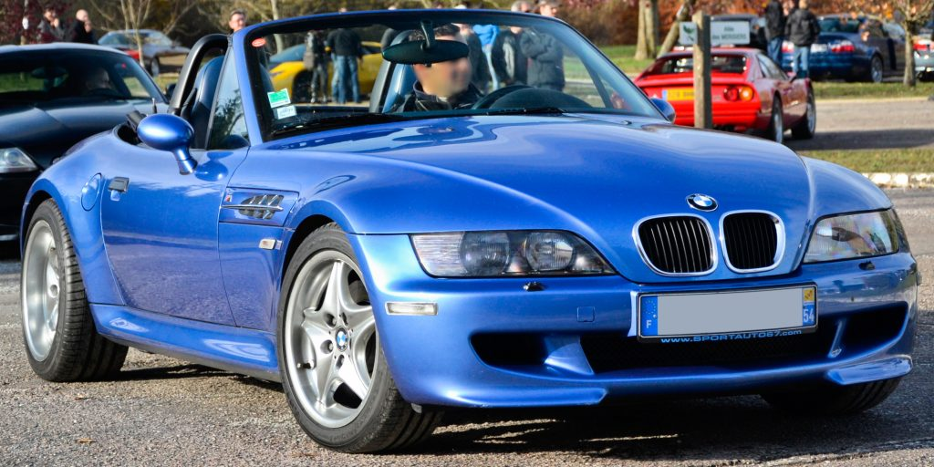 A blue 1997 BMW Z3 M Roadster is parked with its convertible top down in a parking lot.