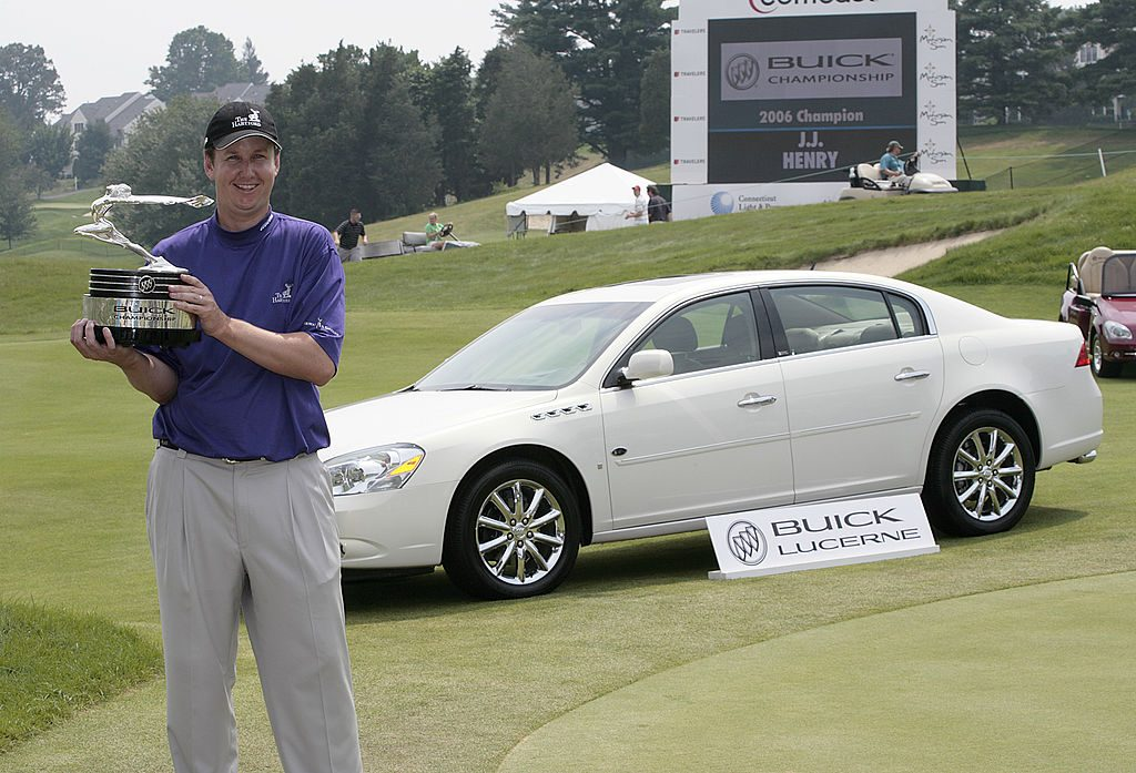 J.J. Henry stands in front of a Buick Lucerne with the trophy after winning the Buick Championship