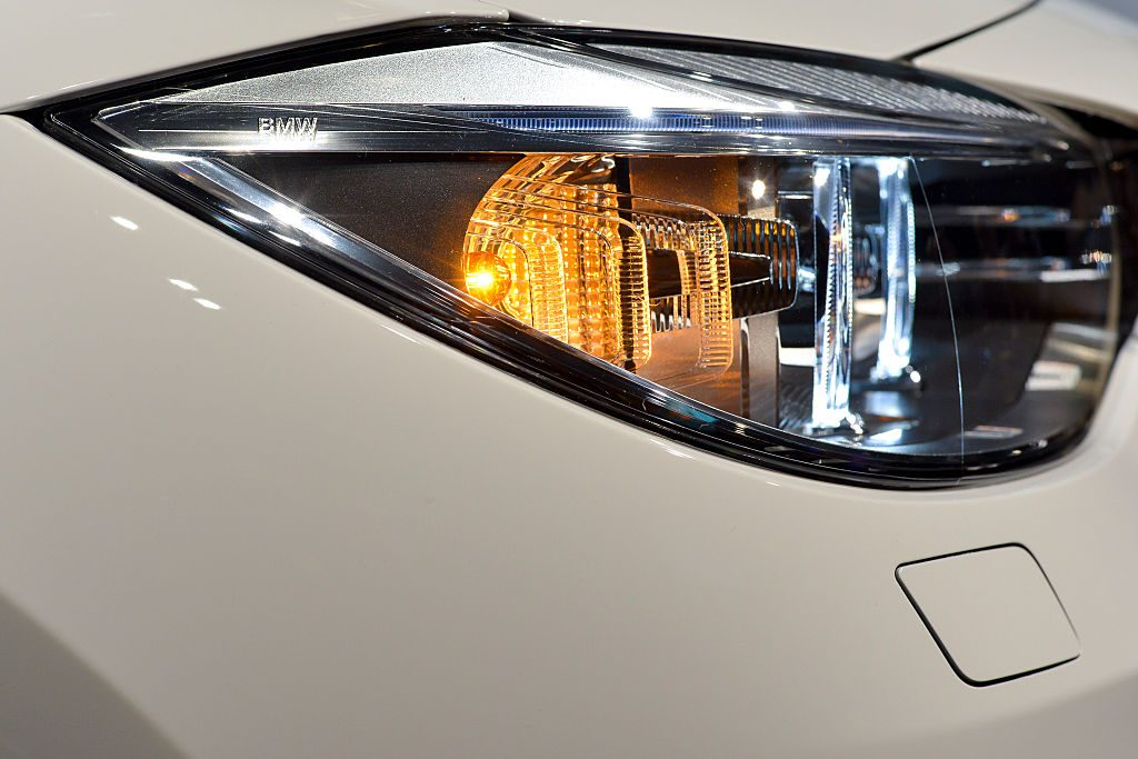 Close up photo of a front head lamp and illuminated turn signal on a white BMW