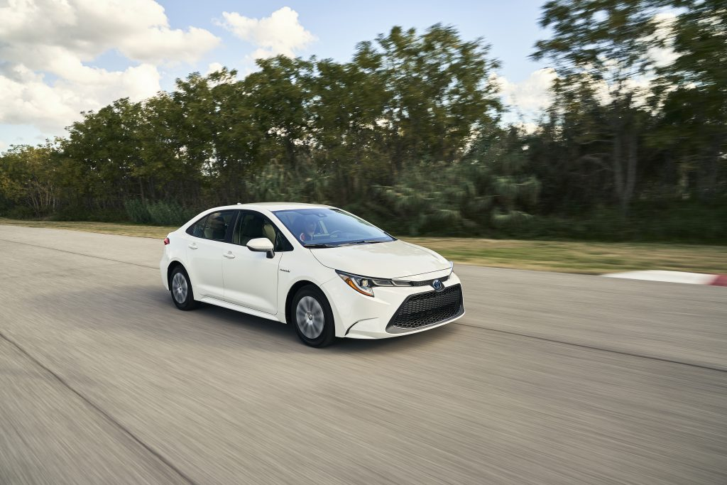 a white 2020 Toyota Corolla at speed on a scenic road
