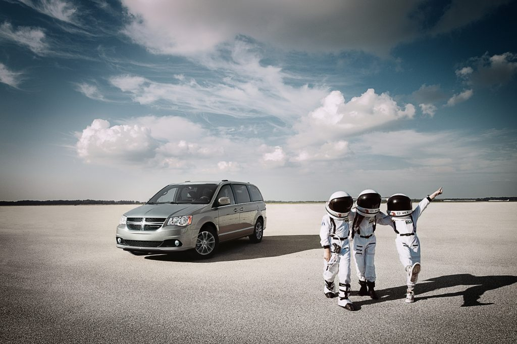 Astronauts standing near the Grand Dodge Caravan