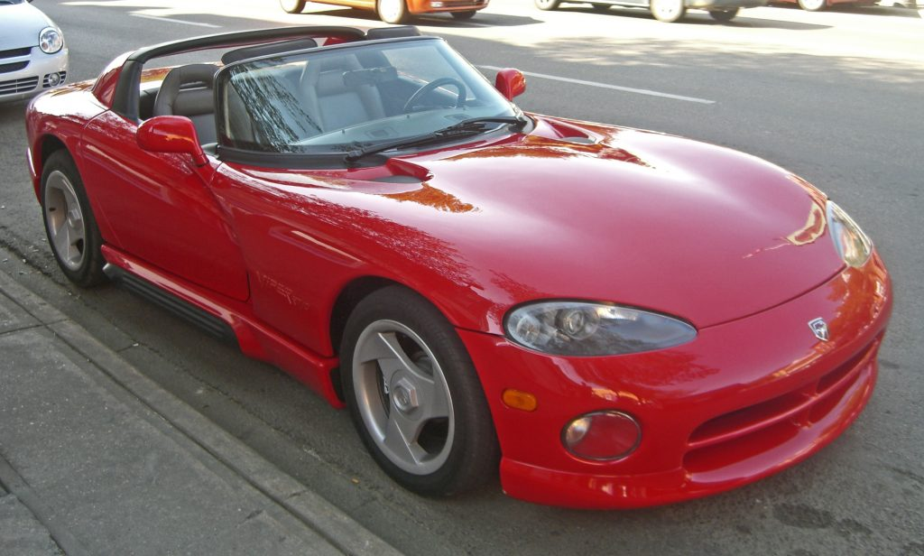 A red 1993 Dodge Viper RT/10 is parked by the side of an urban street.