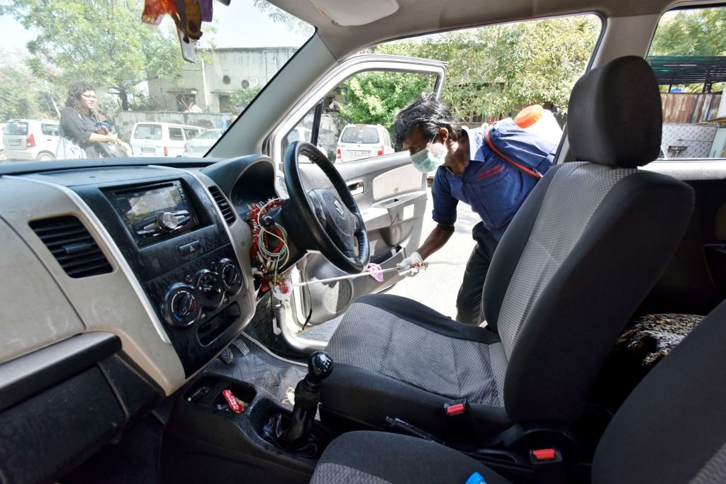 DTC cleaning staff chemically disinfect and sanitize a taxi as a precautionary measure in view of coronavirus concerns