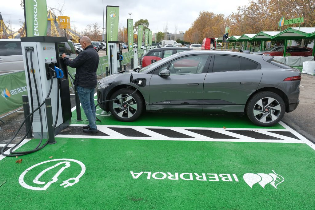 A man charges an electric car at an electric car charging station set up ahead of the UNFCCC COP25 climate conference