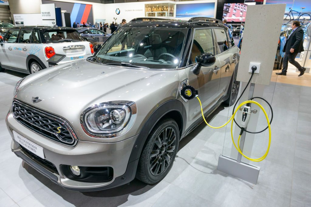A silver Mini Cooper SE Electric plugged into a charger.