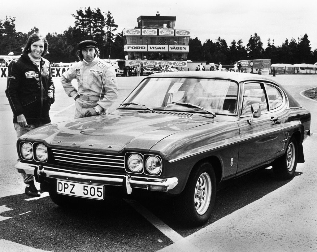 Race Car Drivers Jackie Steward and Emerson Fittipaldi standing in front of their Ford Capri.