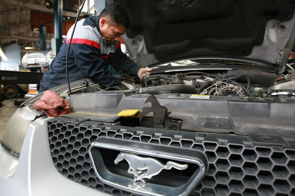 A mechanic working on a Ford Mustang