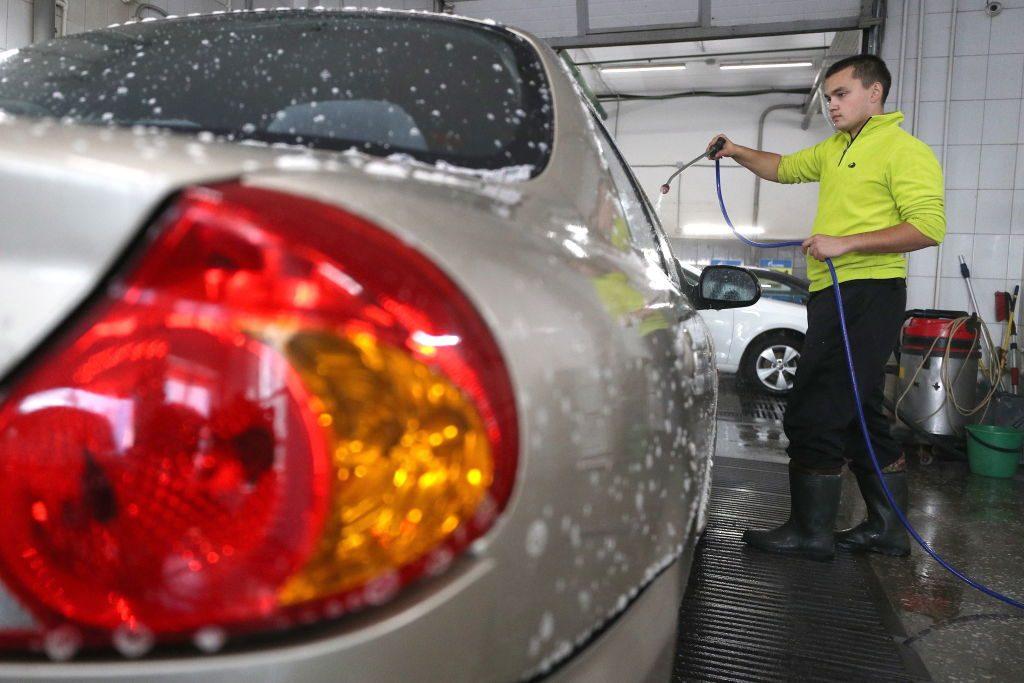 A man washes a silver car.