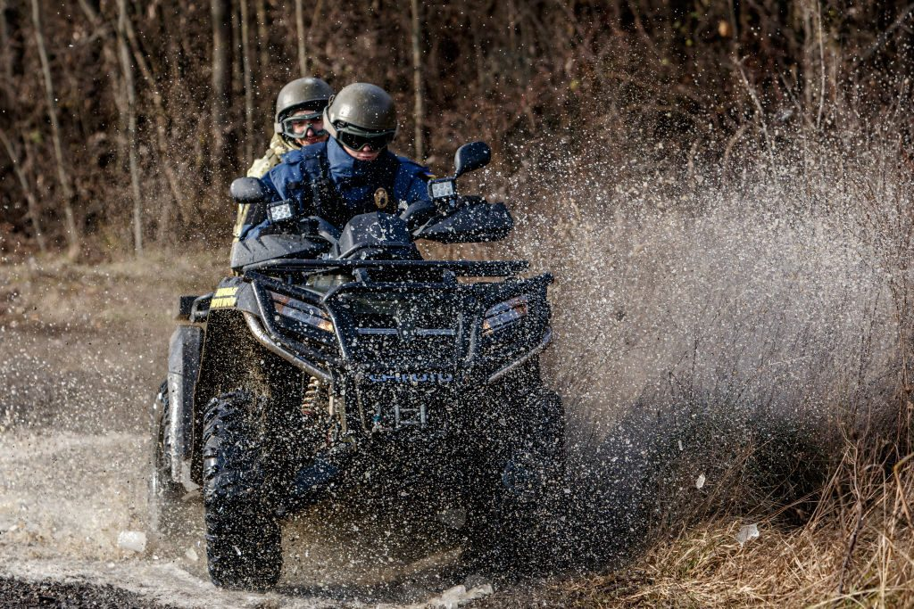 Two people drive an ATV through a muddy creek.