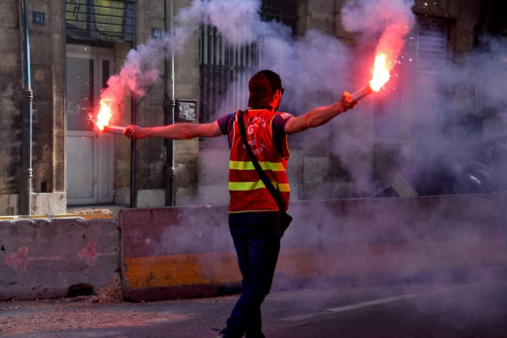 A man holds up emergency road flares to alert drivers of his disabled vehicle.