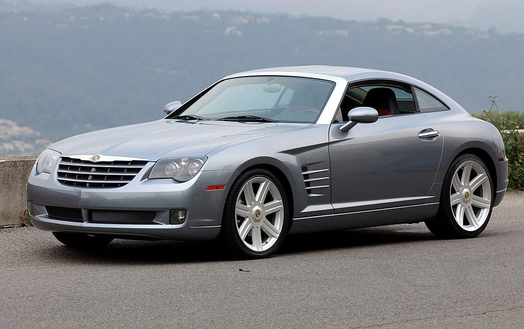 A silver 2003 Chrysler Crossfire coupe parked by a scenic outlook.