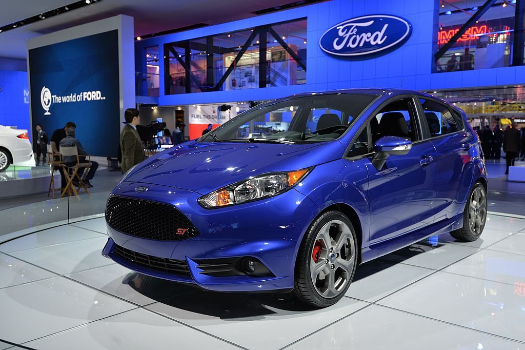 A blue first-generation Ford Fiesta ST displayed at an autoshow.
