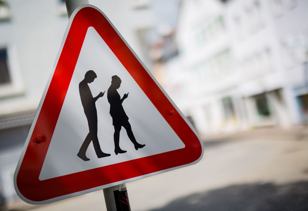 A street sign warning drivers of distracted pedestrians crossing.
