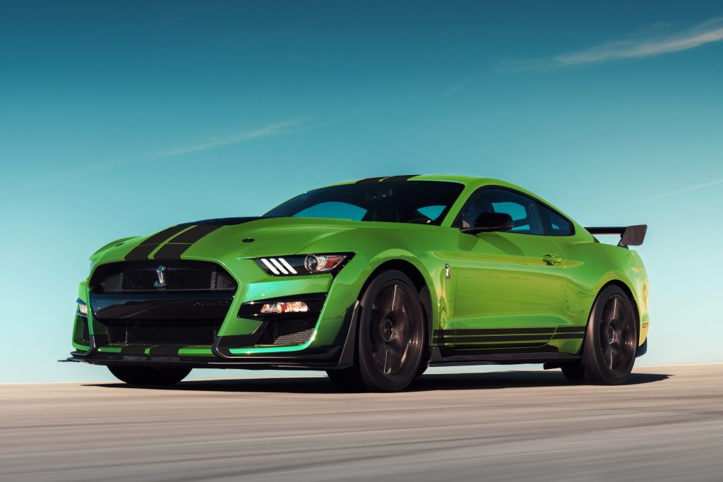 A lime green 2020 Ford Mustang driving down a race track.