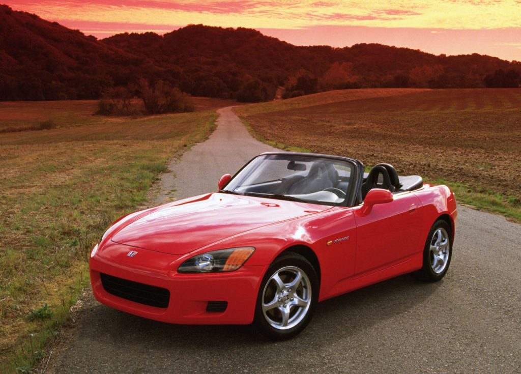 Red 2000 Honda S2000 with the top down on a back-country road