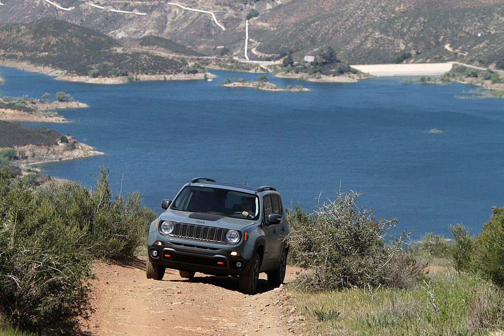 Jeep Renegade driving up dirt road near beach