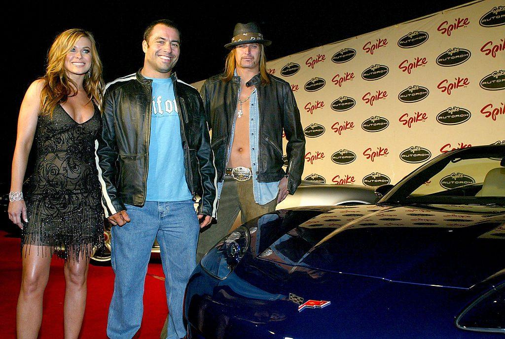 Carmen Electra, Joe Rogan, and Kid Rock standing next to a sports car