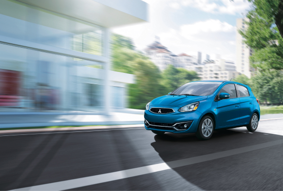 A blue 2020 Mitsubishi Mirage hatchback driving through a city.