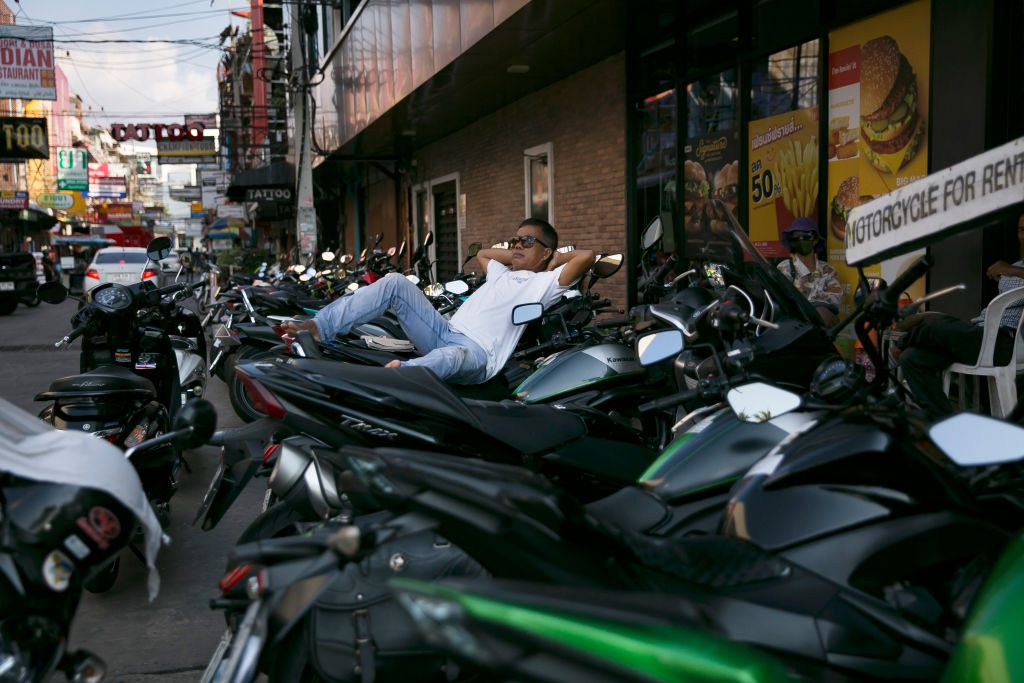 A man reclines at a spot for motorbike rentals